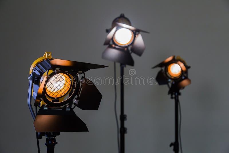 Drei Halogenscheinwerfer mit Fresnellinsen auf einem grauen Hintergrund Fotografieren und Filmen im Innenraum stockfoto