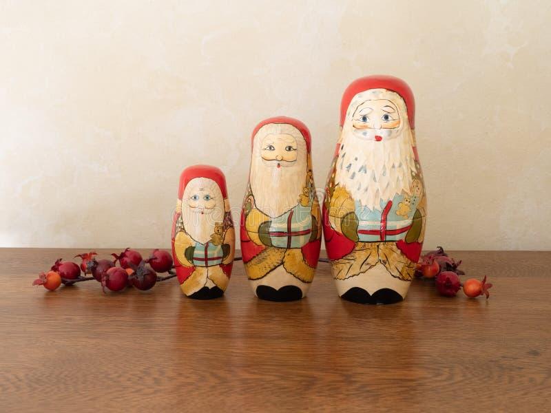 Drei handgemalte hölzerne Santa Claus Dolls mit roten Beeren lizenzfreie stockbilder