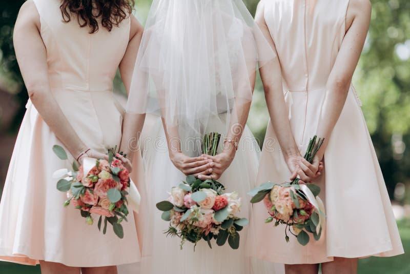 drei Heiratsblumensträuße, die von einer Braut und von ihren Brautjungfern gehalten werden lizenzfreie stockfotos
