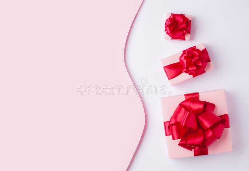Drei helle rosa Pastellk?sten gebunden mit einem roten Satinband mit einem Knallknallbogen lizenzfreie stockbilder