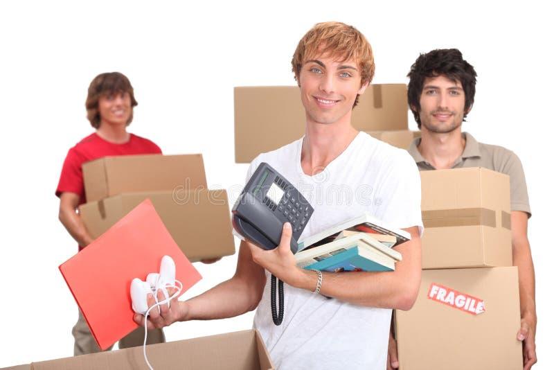 Drei Housemates, die heraus ihre Wohnung bewegen stockfotografie