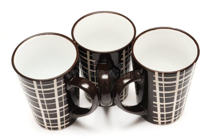 Drei identische gro?e hohe dunkelbraune Kaffeetassen mit einfachen Linien entwerfen stockfotografie