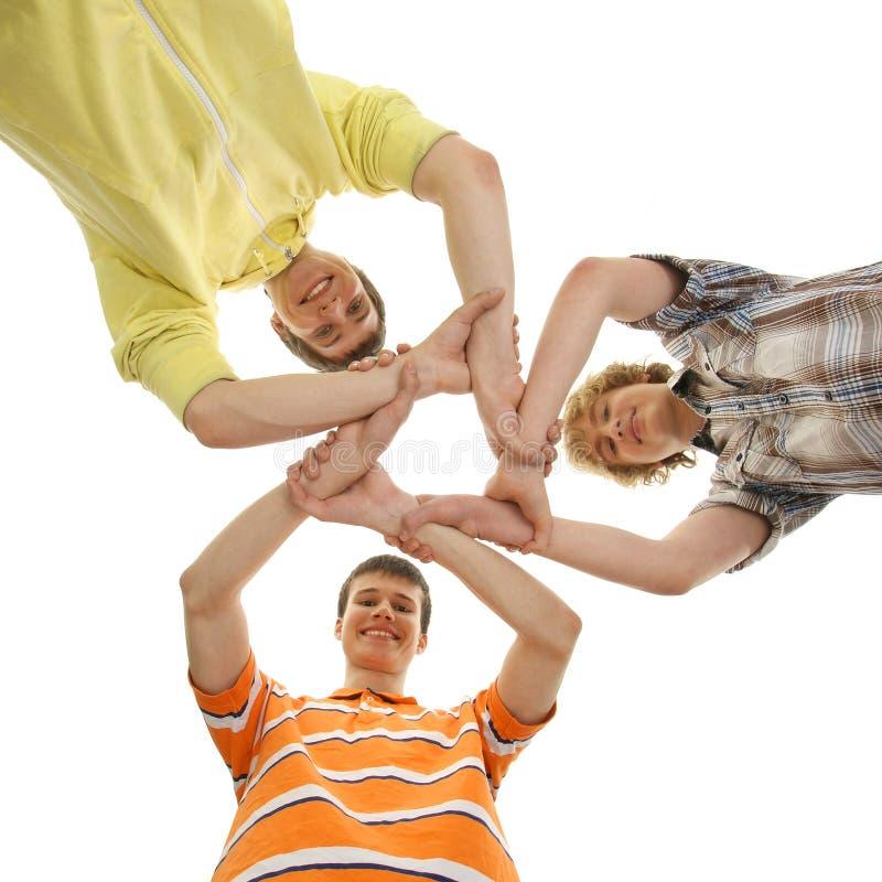 Drei jugendlich Jungen, die in einer Form eines Sternes anhalten lizenzfreie stockbilder