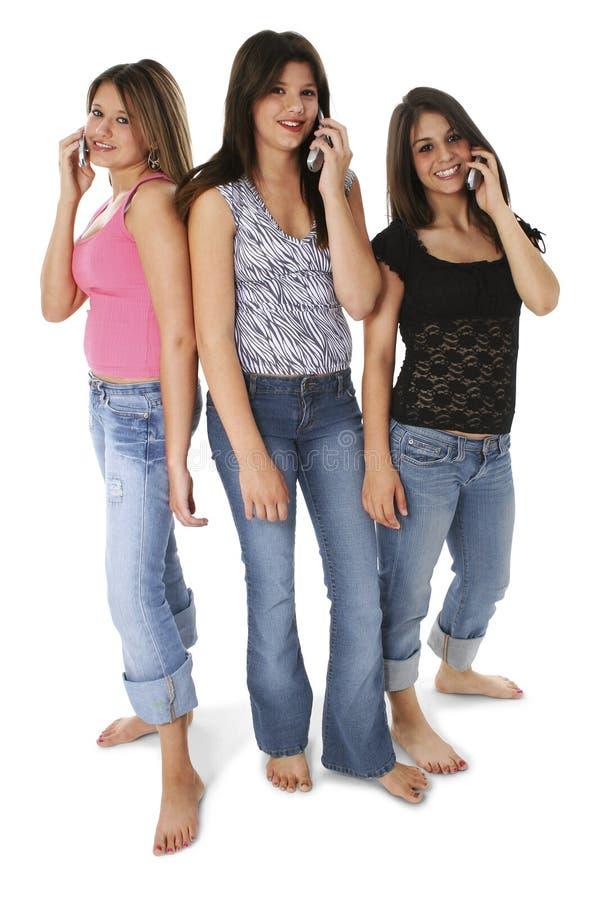 Drei jugendlich Mädchen mit Mobiltelefonen über Weiß stockbilder