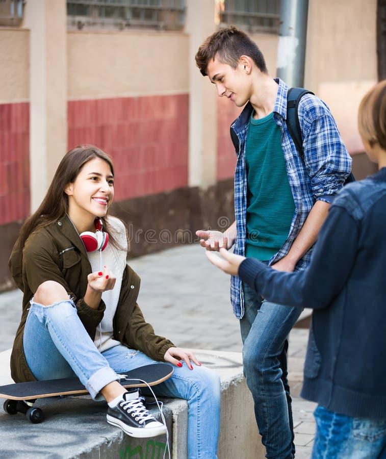 Drei Jugendliche, die heraus draußen hängen stockbilder