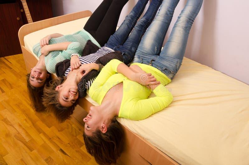 Drei Jugendlichen, die Spaß auf dem Bett haben stockbild