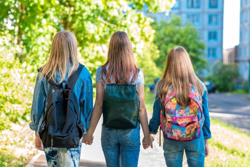 Drei Jugendlichen Sie halten sich ` s Hände Rückkehr steuert nach der Schule automatisch an Sommer in der Natur Hinter Rucksäcken lizenzfreies stockbild