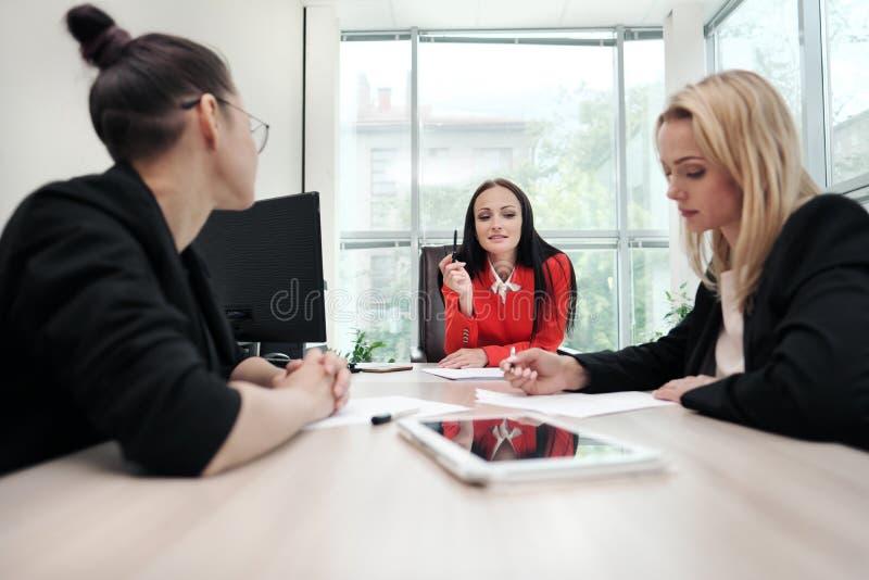 Drei junge attraktive Frauen in den Anzügen sitzen an einem Schreibtisch und besprechen Arbeitsflüsse Kopf und Untergebene lizenzfreies stockfoto