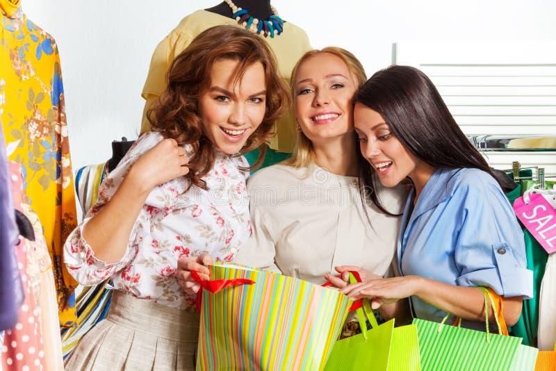 Drei junge aufgeregte Frauen mit Einkaufstaschen lizenzfreie stockfotos
