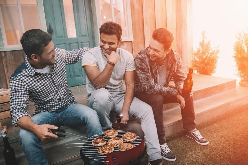 Drei junge Bier trinkende und beim Sitzen lächelnde Männer auf Portal lizenzfreies stockfoto