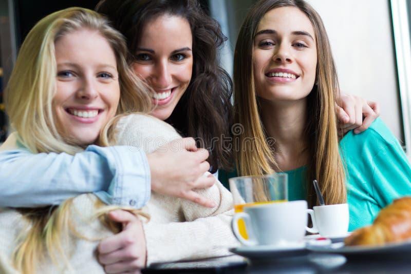 Drei junge Frauen, die Kaffeepause haben lizenzfreie stockfotografie