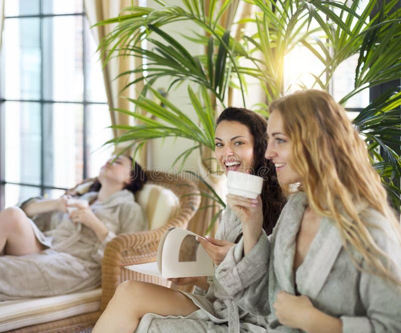 Drei junge Frauen, die Tee am Kurort trinken stockfotografie
