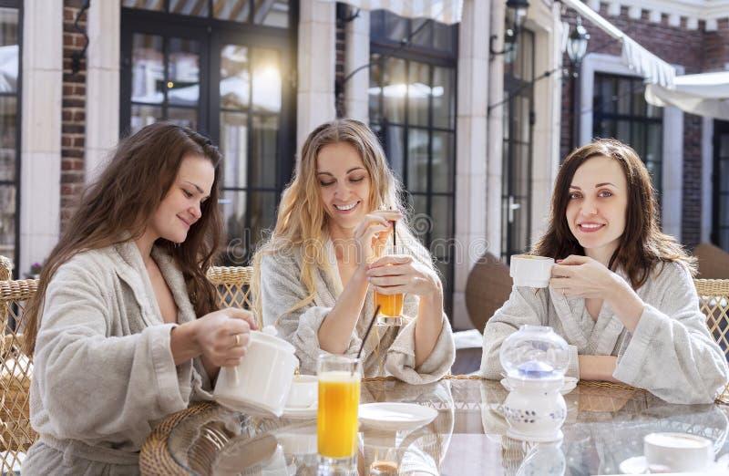 Drei junge Frauen, die Tee am Kurort trinken lizenzfreies stockfoto
