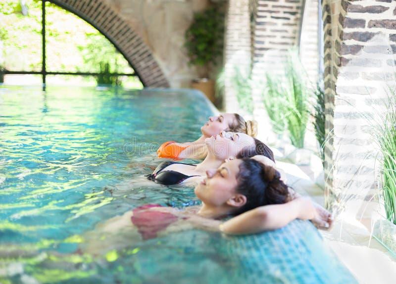 Drei junge Frauen im Swimmingpool lizenzfreie stockbilder