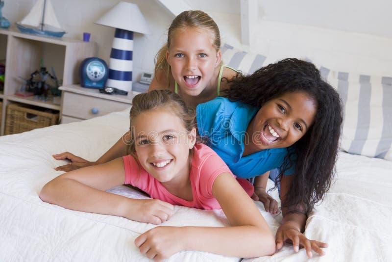 Drei junge Freunde, die oben auf einander liegen lizenzfreies stockbild