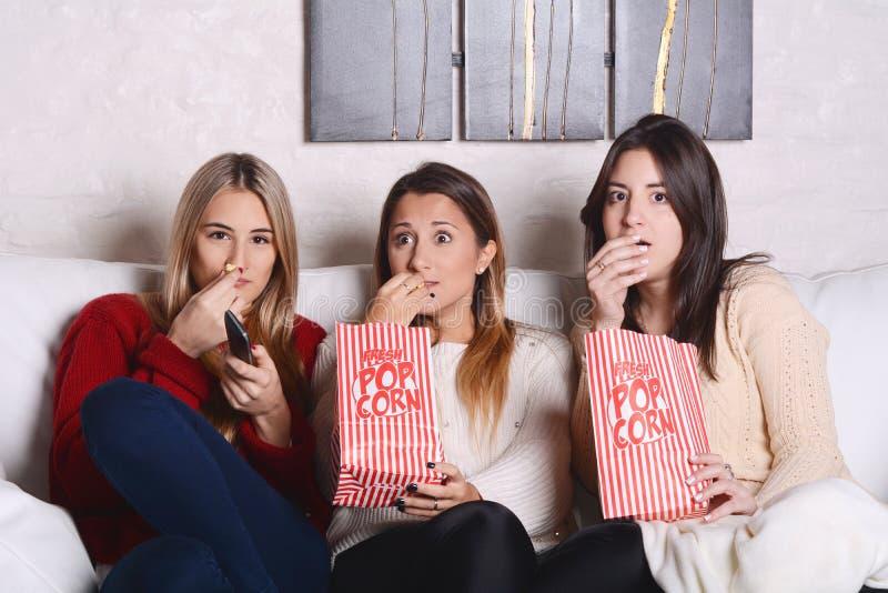 Drei junge Freunde, die Popcorn essen und Filme aufpassen stockbilder