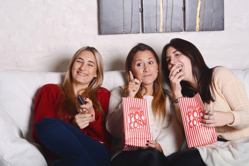 Drei junge Freunde, die Popcorn essen und Filme aufpassen lizenzfreie stockfotografie