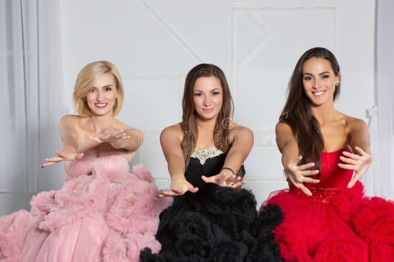 Drei junge Freundinnen, die im Studio aufwerfen stockbilder