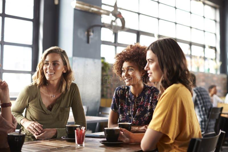 Drei junge Freundinnen, die Sit At Table In Coffee-Geschäft und -gespräch treffen lizenzfreies stockbild