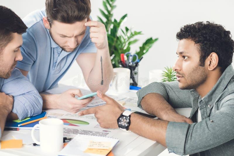 Drei junge Geschäftsmänner, die bei Tisch sitzen und zusammen an neuem Projekt arbeiten stockbilder
