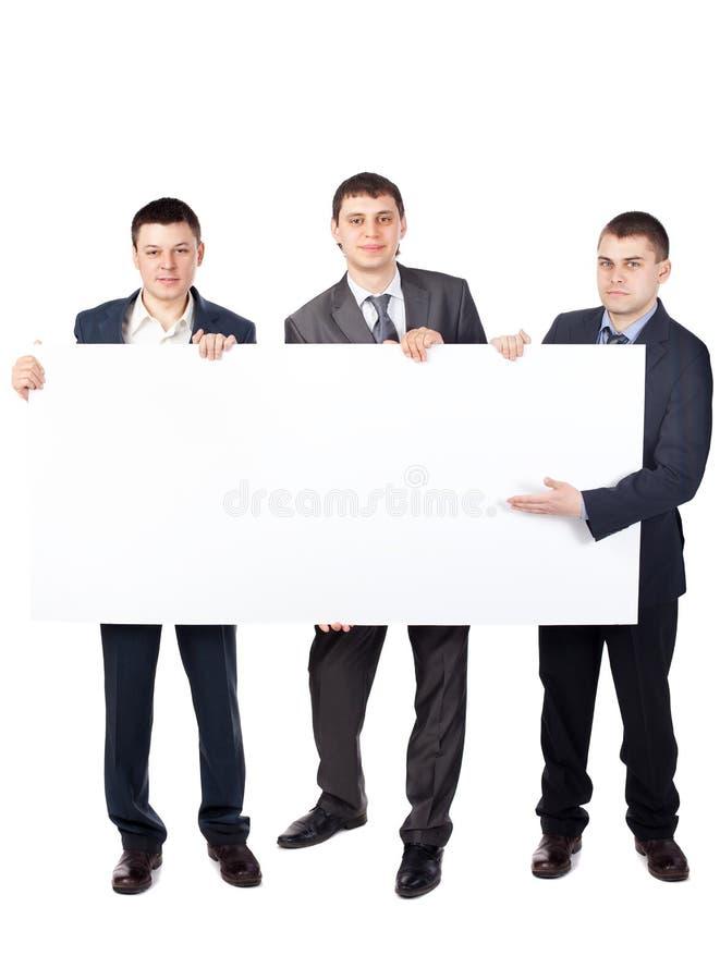 Drei junge Geschäftsmänner halten ein großes unbelegtes Zeichen lizenzfreies stockbild