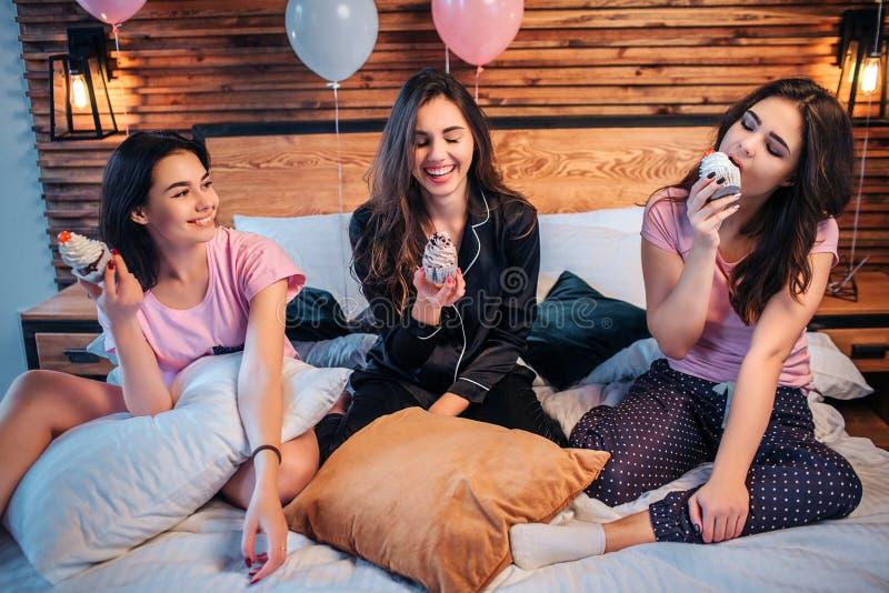 Drei junge glückliche Frauen sitzen auf Bett Zwei von ihnen Blick auf akes und Lächeln Drittes man isst es Kuchen ist köstlich Mä lizenzfreie stockfotos