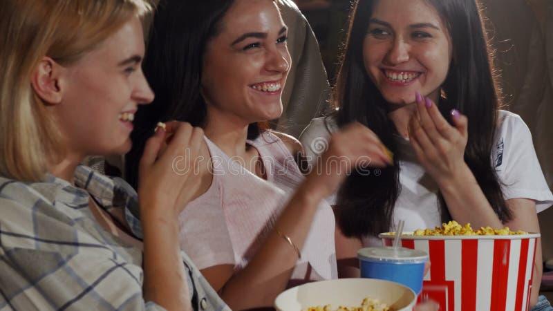 Drei junge lachende Freundinnen beim einen Film zusammen aufpassen stockfoto