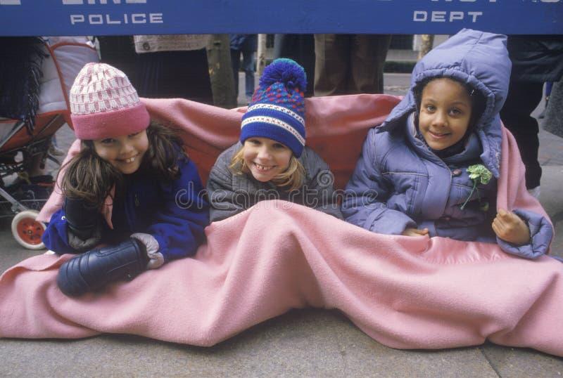 Drei junge Mädchen, die beim Warten auf eine Parade, NY warm bleiben stockfoto