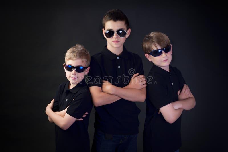 Drei junge Männer im Schwarzen stockfotografie