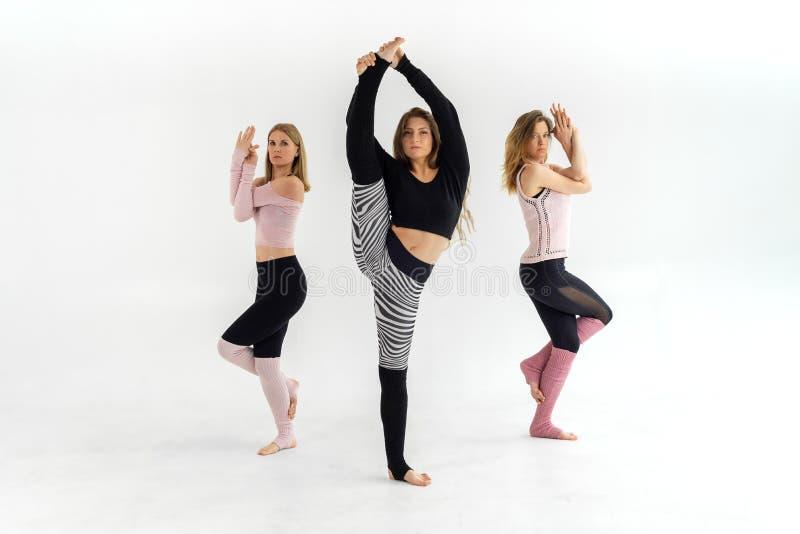 Drei junge schöne Mädchen, die Yoga pilates, ein Mädchen tut das Ausdehnen tun stockbild