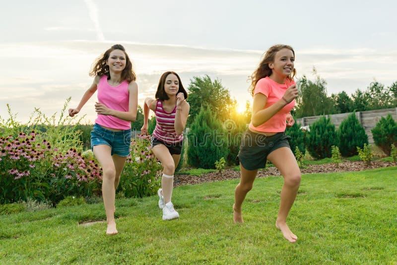 Drei junge Sportmädchenjugendliche, die auf einem grünen Rasen gegen den Hintergrund des Sommersonnenuntergangs laufen stockbilder