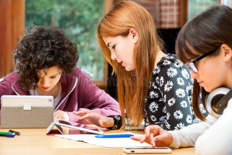 Drei junge Studenten, die an digitalen divices arbeiten. stockbild