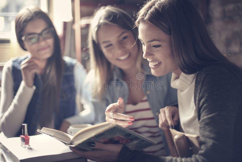 Drei junge Studenten, die zusammen sitzen und Lesebuch lizenzfreie stockbilder