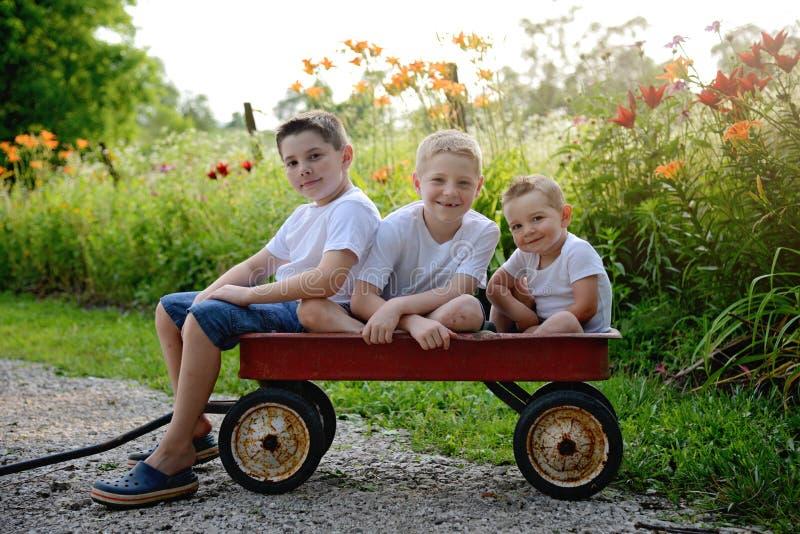 Drei Jungen, die in einem roten Lastwagen sitzen stockbild
