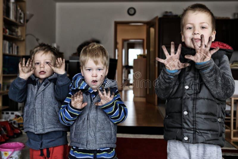 Drei Jungen mit den sehr schmutzigen Händen, nachdem sie geändert haben, ermüdet stockfoto