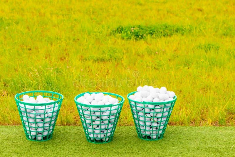 Drei Körbe gefüllt mit Golfbällen auf dem Gras stockfotos