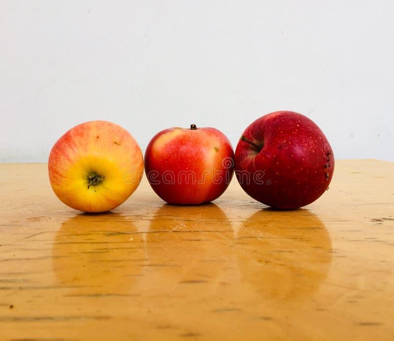drei köstliche Äpfel auf Holztisch stockfoto