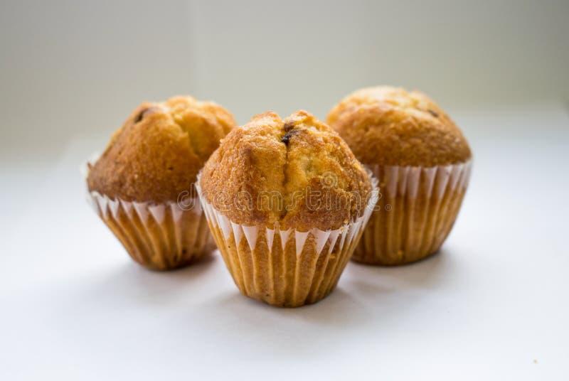 Drei köstliche Muffins auf einem weißen Hintergrund stockfotos