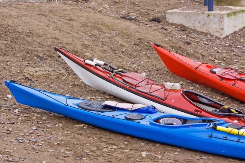 Drei Kajaks auf dem Ufer lizenzfreie stockfotografie