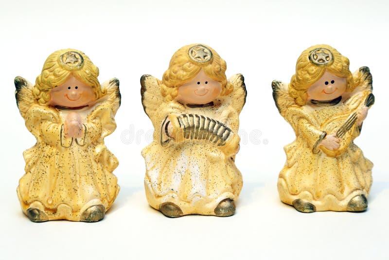 Drei keramische Figürchen von Engeln färben sich auf einem weißen Hintergrund gelb stockfotos