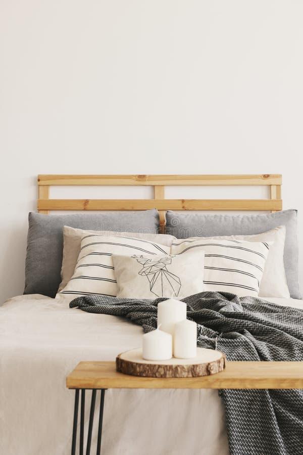 Drei Kerzen auf dem Holztisch nahe bei gemütlichem Bett mit kopierten Kissen und grauer Decke, wirkliches Foto lizenzfreie stockfotos