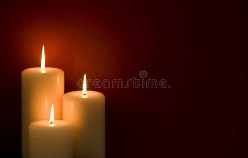 Drei Kerzen Rot Hintergrund- stockbilder