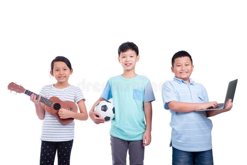 Drei Kinder, die über weißem Hintergrund lächeln stockbilder