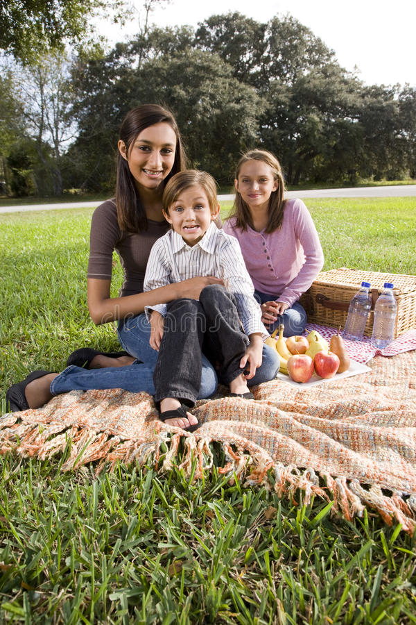 Drei Kinder, die auf Picknickdecke im Park sitzen lizenzfreies stockbild