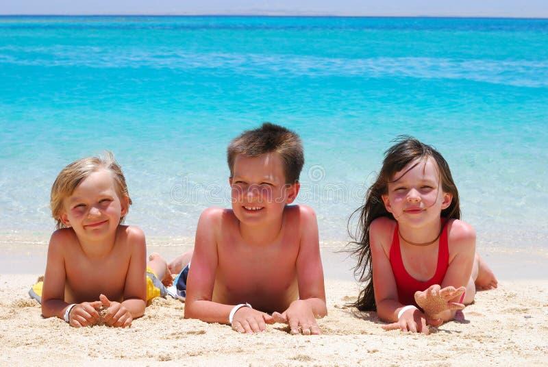 Drei Kinder, die auf Strand liegen lizenzfreies stockfoto