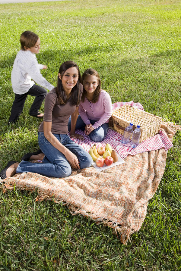 Drei Kinder, die ein Picknick am Park haben stockfotos