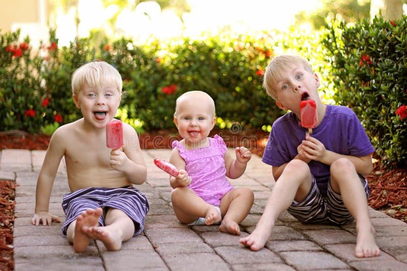 Drei Kinder, die Frucht-Eis am Stiel draußen am Sommer-Tag essen stockfoto