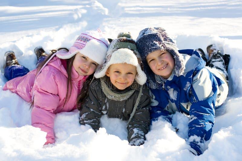 Drei Kinder, die im frischen Schnee spielen lizenzfreies stockfoto