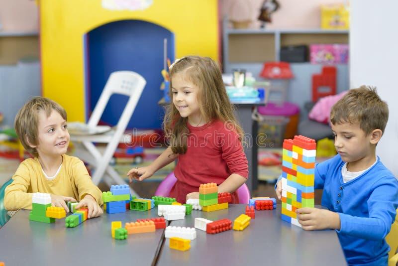Drei Kinder, die am Kindergarten spielen lizenzfreies stockfoto