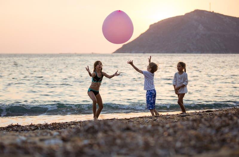Drei Kinder, die mit enormem rosa Ballon auf Strand bei Sonnenuntergang spielen lizenzfreie stockfotos
